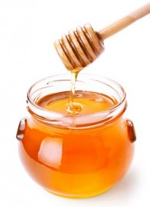 Glass jar of honey with wooden drizzler isolated on white background